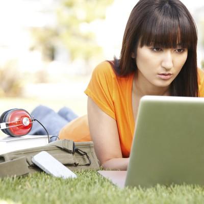 junge frau sitzt an einem laptop mit kopfhoerern daneber