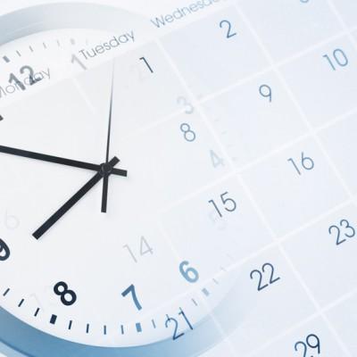 eine uhr die hinter einem durchsichtigen kalender verschwindet