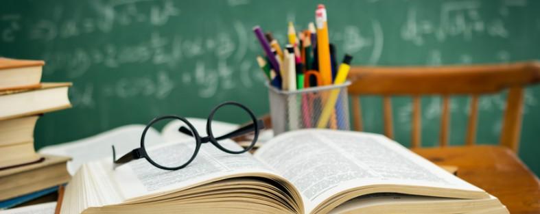 schreibtisch mit Buechern vor einer Schulafel