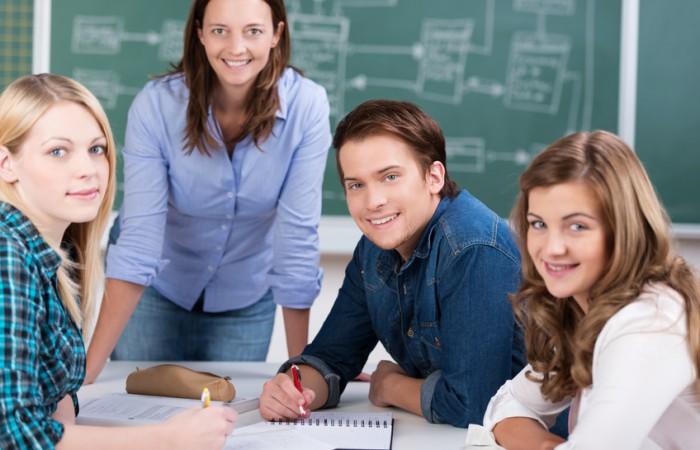 eine gruppe schueler mit lehrerin vor einer tafel