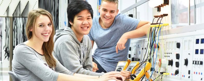 gruppe junger lehrlinge sitzen vor elektronischen geraeten