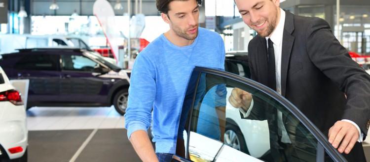 Verkaufsgespraech im Autohaus Verkaeufer beraet Kunden beim Kauf eines Neuwagen