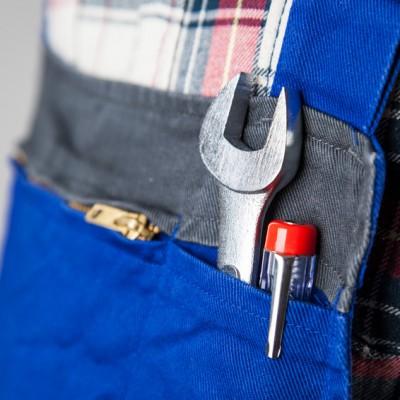 schraubenschluessel und schraubenzieher in einer tasche bei einem arbeiter