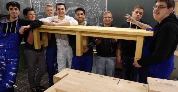 neue schueler der schulerfirma bauen und halten zusammen eine bank vor einer tafel