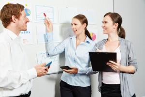 Gruppe Geschaeftsleute plant zusammen Investition mit Diagrammen im Büro