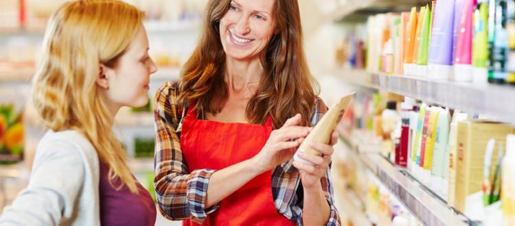 Junge Frau in einer Drogerie bekommt Beratung beim Kauf von Kosmetika von einer Verkaeuferin