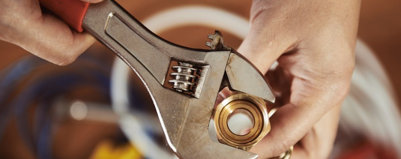 klempner schraubt mit einem schraubenschluessel etwas fest
