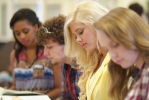 studenten sitzen gemeinsam an einem tisch und lesen ein buch