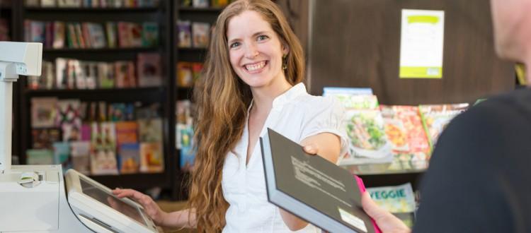 Kassiererin an der Kasse eines Buchladens oder Buchhandlung verkauft einem Kunden ein Buch